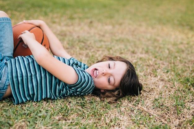 Vue côté, de, enfant, coucher dans herbe Photo gratuit