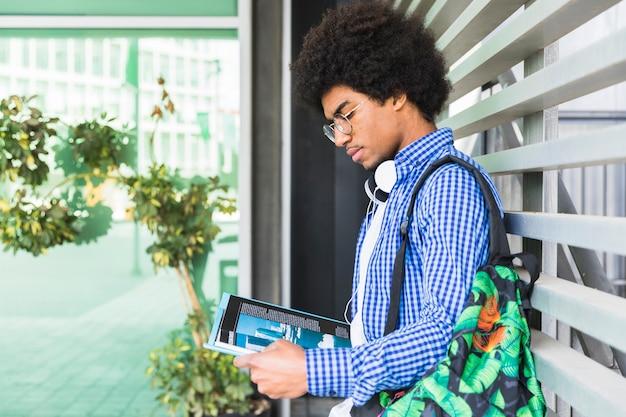 Vue de côté d'un étudiant adolescent portant un sac sur son épaule, appuyé contre le mur, lisant le livre Photo gratuit