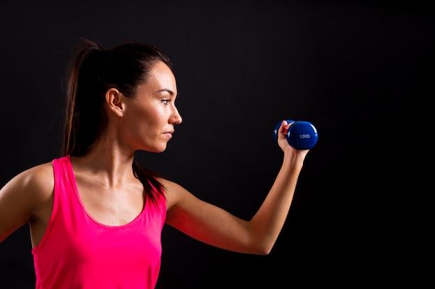 Vue de côté de l'exercice féminin avec des poids Photo gratuit