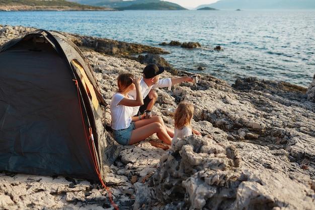 Vue De Côté De La Famille Sympathique Assis Près De La Tente à Rock Beach, Admirant La Mer. Photo Premium