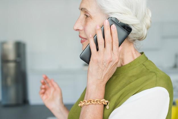 Vue côté, de, femme aînée, conversation téléphone portable Photo gratuit