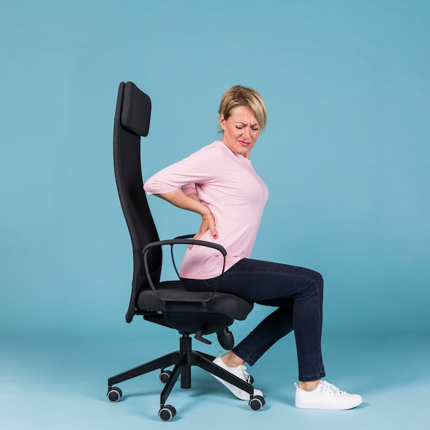 Vue de côté d'une femme assise sur une chaise, souffrant de maux de dos Photo gratuit