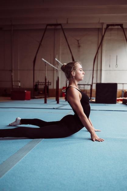 Vue De Côté Femme Blonde Formation Pour Les Jeux Olympiques De Gymnastique Photo gratuit
