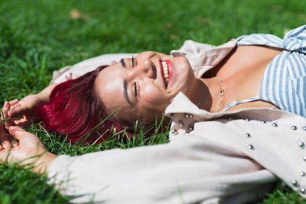Vue côté, de, femme, coucher herbe Photo gratuit