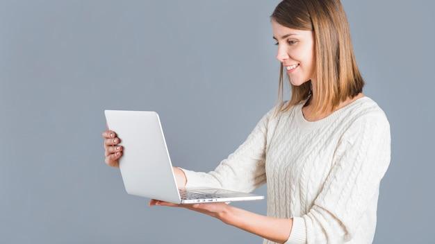 Vue de côté d'une femme heureuse tenant un ordinateur portable sur fond gris Photo gratuit