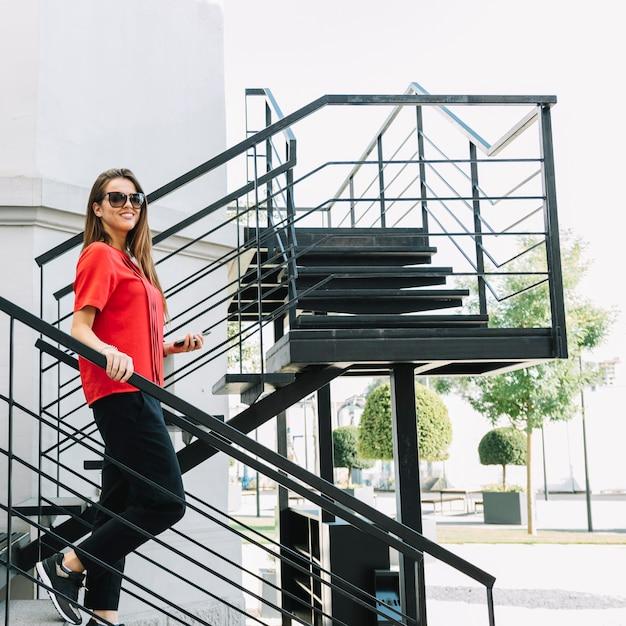 Vue de côté d'une femme à la mode en descendant l'escalier Photo gratuit