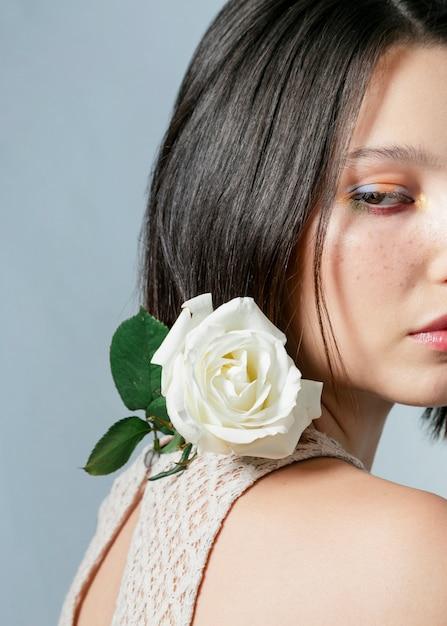 Vue côté, de, femme pose, à, blanc rose Photo gratuit