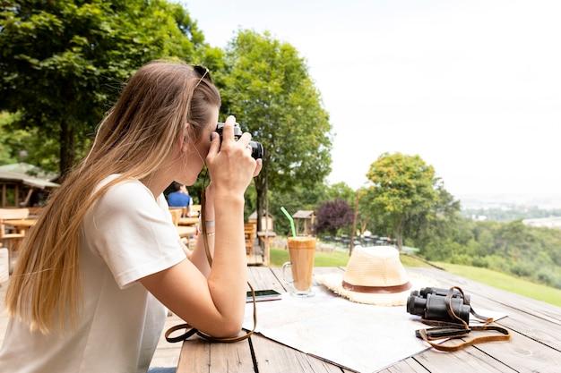 Vue de côté d'une femme prenant une photo Photo gratuit