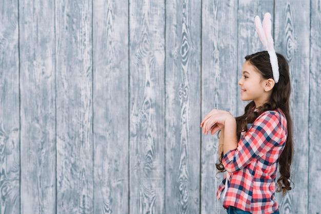Vue côté, de, a, fille, poser, comme, lapin, devant, bois, toile de fond gris Photo gratuit