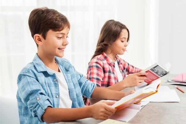 Vue de côté des frères et sœurs étudiant le temps à la maison Photo gratuit