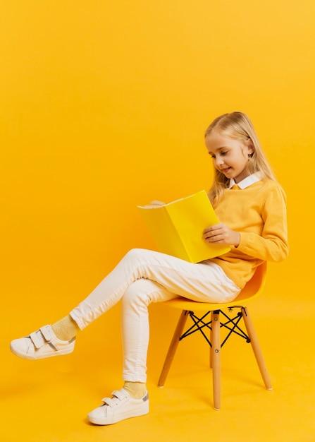 Vue Côté, De, Girl, Poser Chaise, Pendant, Lecture Livre Photo gratuit