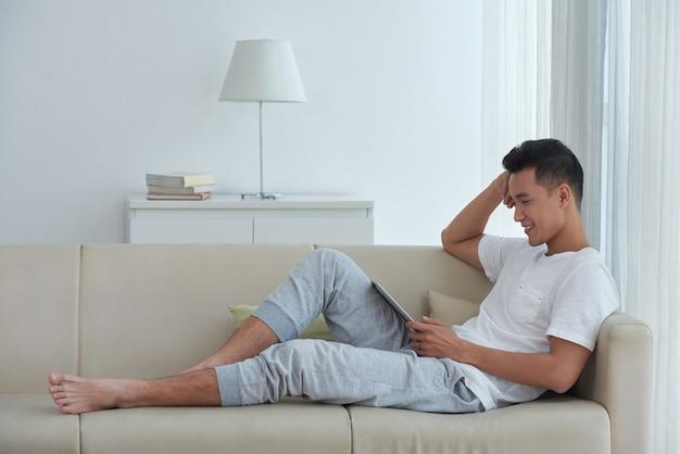 Vue de côté d'un homme asiatique assis confortablement sur le canapé et en regardant une vidéo sur son pavé numérique Photo gratuit
