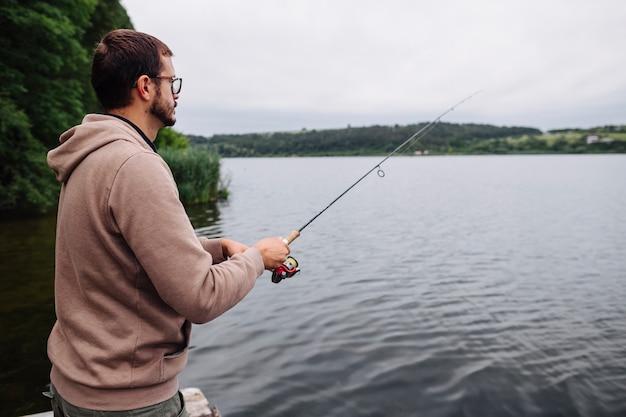 Vue de côté de l'homme de pêche dans le lac idyllique Photo gratuit