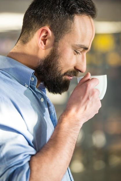 Vue de côté de l'homme avec une tasse de café à travers le verre. Photo Premium