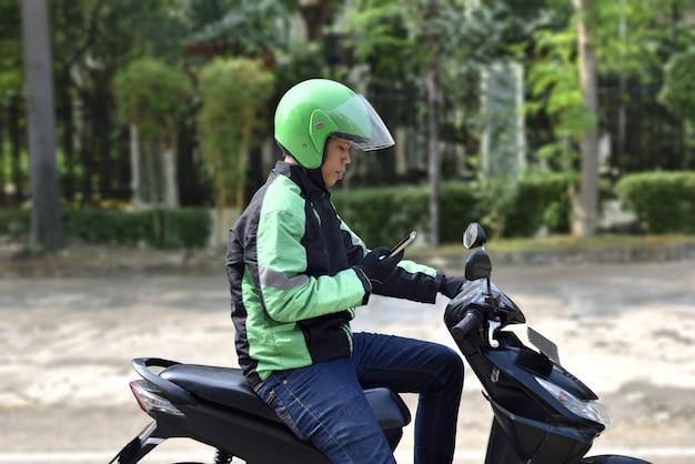 Vue de côté d'un homme de taxi moto asiatique vérifiant le téléphone Photo Premium