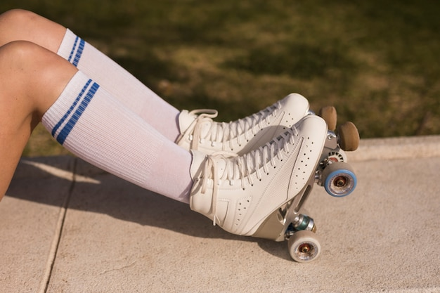 Vue de côté d'une jambe de femme avec un patin à roulettes blanc Photo gratuit