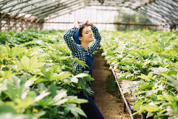 Vue de côté d'un jardinier féminin heureux debout dans une serre Photo gratuit