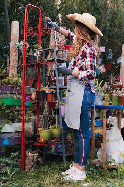 Vue de côté d'une jardinière femme portant un chapeau organisant les plantes en pot dans le support rouge Photo gratuit