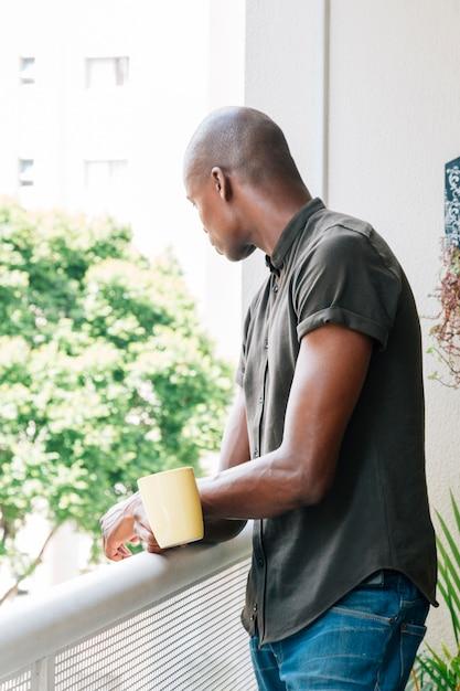 Vue côté, de, a, jeune africain, debout, sur, les, balcon, tenant tasse café, dans main Photo gratuit