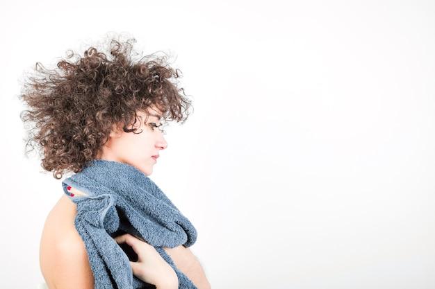 Vue de côté de la jeune femme aux cheveux bouclés essuie son corps avec une serviette sur fond blanc Photo gratuit