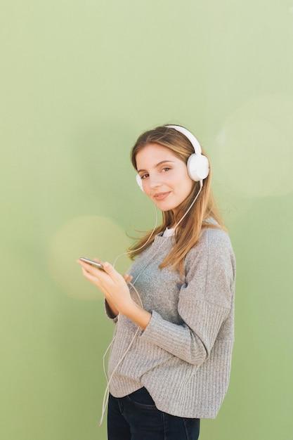 Vue Côté, De, A, Jeune Femme Souriante, écoute, Musique, Sur, Casque, Contre, Fond Vert Photo gratuit