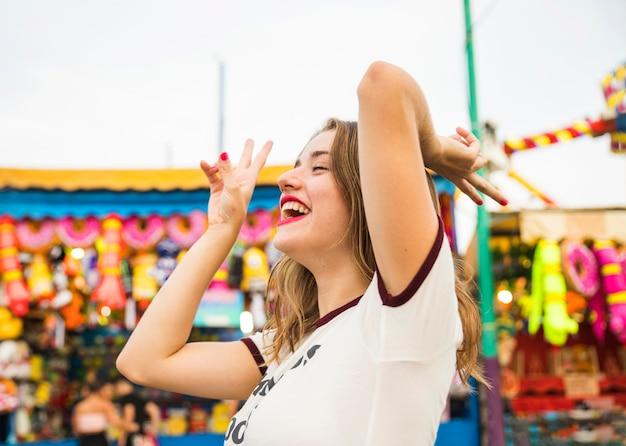 Vue de côté d'une jeune femme souriante gesticulant signe de paix Photo gratuit