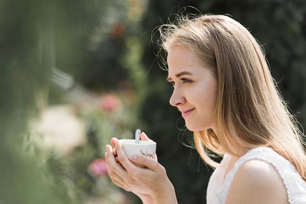 Vue de côté d'une jeune femme tenant une tasse de café à deux mains Photo gratuit