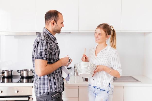 Vue côté, de, a, jeune homme, aider, sa, femme, préparer nourriture, dans, cuisine Photo gratuit