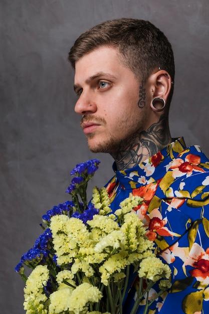 Vue de côté d'un jeune homme avec les oreilles percées et le nez tenant une fleur de limonium jaune et bleu sur fond gris Photo gratuit