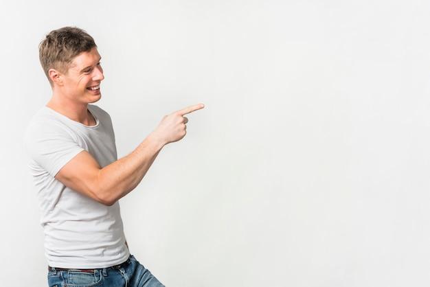 Vue de côté d'un jeune homme souriant, pointant son doigt sur quelque chose sur un fond blanc Photo gratuit
