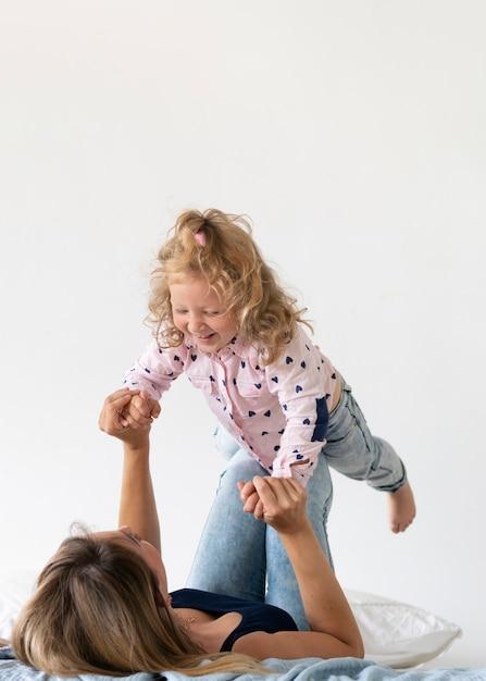 Vue côté mère jouant avec une fille heureuse Photo gratuit
