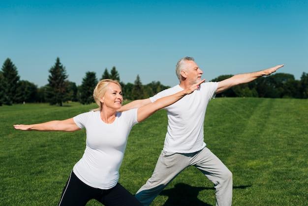 Vue de côté personnes âgées exerçant en plein air Photo gratuit