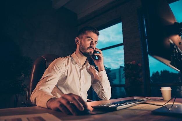 Vue De Côté De Profil De Travailleur Concentré S'asseoir à Table De Travail De Bureau Sur Son Smartphone Photo Premium