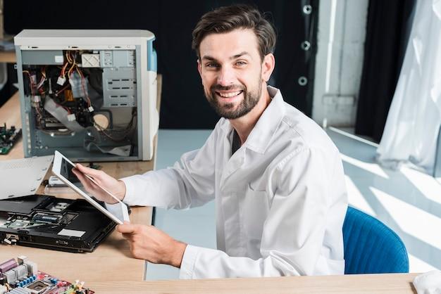 Vue de côté d'un technicien de sexe masculin heureux tenant une tablette numérique en atelier Photo gratuit