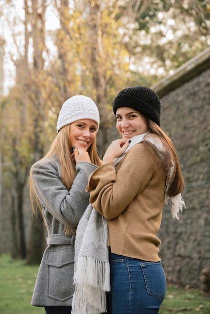 Vue de côté tir moyen de deux femmes souriantes dans le parc Photo gratuit