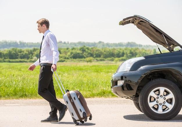 Vue de côté toute la longueur du jeune homme d'affaires avec valise. Photo Premium