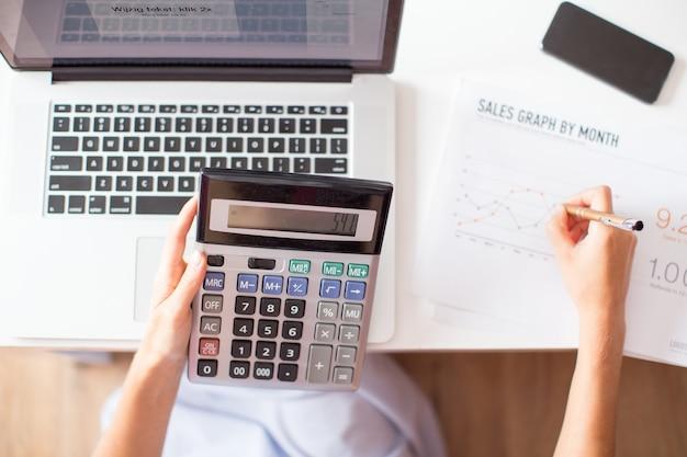 Vue croisée du gestionnaire des ventes utilisant la calculatrice Photo gratuit