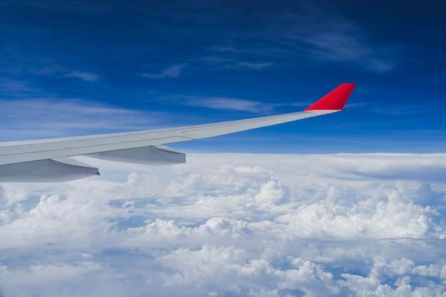 Vue depuis la fenêtre de l'avion et l'aile avec des nuages duveteux, volant et voyageant Photo Premium