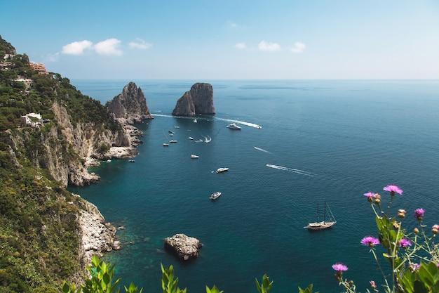 Vue depuis les jardins d'auguste sur la côte de capri et les rochers de faraglioni. Photo Premium