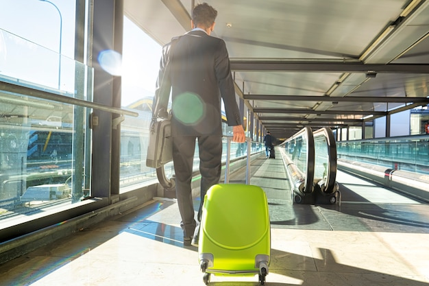 Vue De Derrière D'un Jeune Homme D'affaires Habillé En Costume Voyageant En Avion Avec Son Sac De Roue Sur Les Escalators De L'aéroport Photo Premium