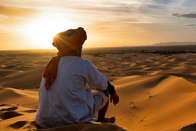 Vue de derrière d'un jeune indigène du désert qui observe les dunes du maroc au coucher du soleil Photo Premium