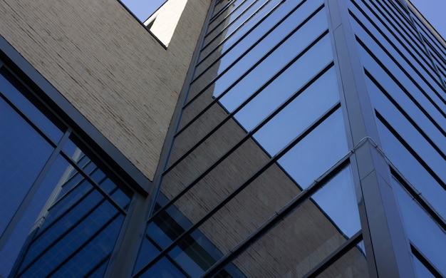 Vue de dessous sur un bâtiment moderne avec des fenêtres en verre Photo Premium