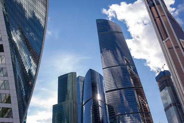 Vue de dessous des gratte-ciel de moscou-city avec un design futuriste avec reflet des nuages Photo Premium