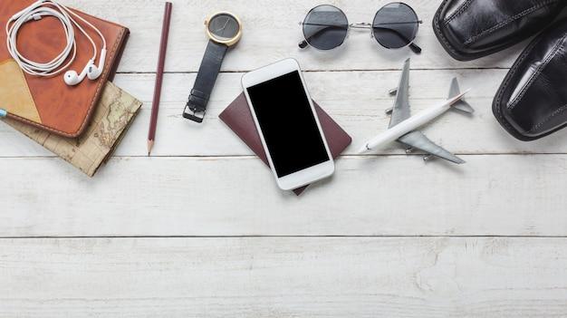 Vue de dessus des accessoires pour voyager concept.white téléphone mobile et casque sur fond en bois.airplane, carte, passeport, regarder sur la table en bois. Photo gratuit