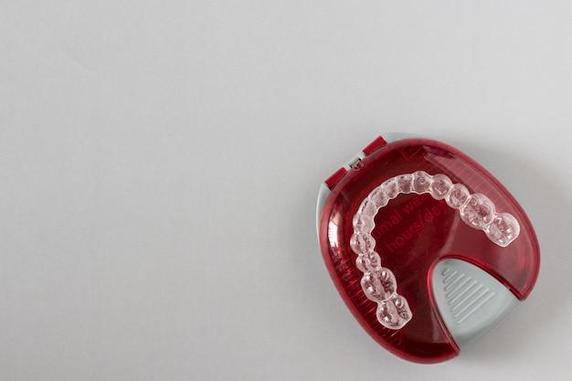 Vue de dessus des accolades invisalign ou des fixations invisibles sur fond gris Photo Premium