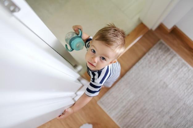 Vue De Dessus De L'adorable Petit Garçon Blond Aux Beaux Yeux Bleus Tenant Sa Bouteille D'eau Et Regardant La Caméra. Photo Premium
