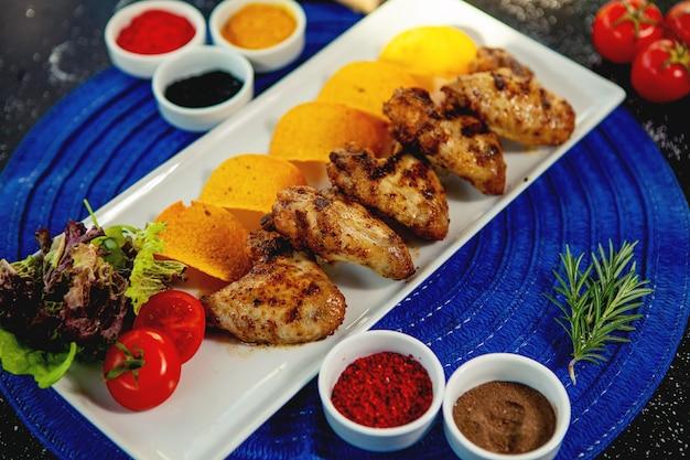Vue de dessus des ailes de poulet grillées servies avec pommes de terre frites et salade fraîche Photo gratuit