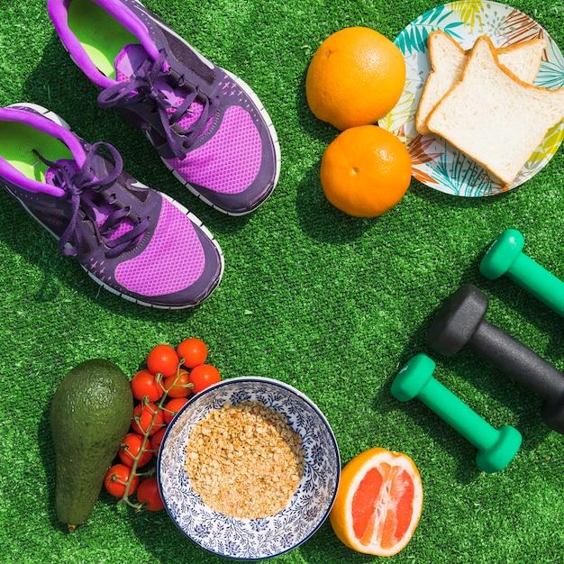 Vue de dessus des aliments sains avec des haltères et une paire de chaussures sur un gazon vert Photo gratuit