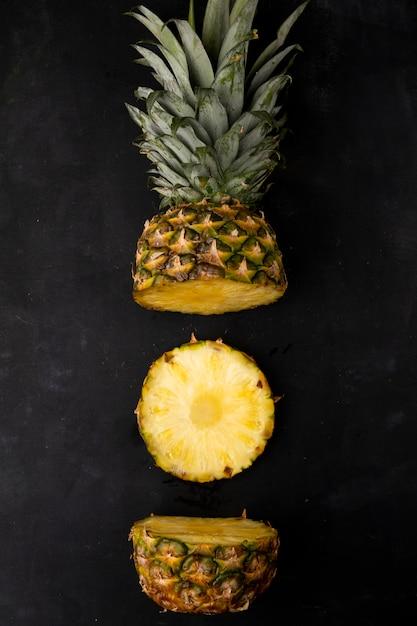Vue De Dessus De L'ananas Coupé Sur Une Surface Noire Photo gratuit