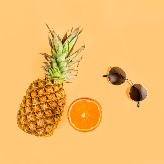 Vue de dessus ananas, orange et lunettes de soleil Photo gratuit